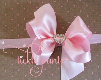 Please make a hairbow to match my sweet baby's birthday tutu. Long tails, center jewel.