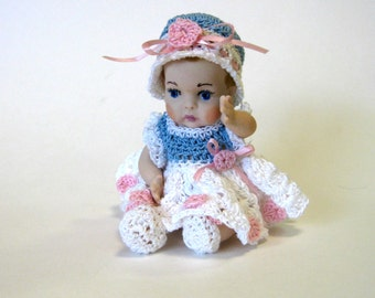 """All porcelain 5"""" handcrafted baby girl in blue and white crocheted dress with roses"""