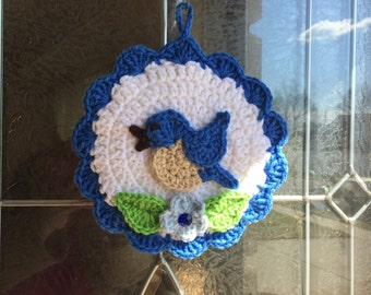 Crocheted springtime bird with forget me not flower
