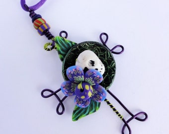Skull Cross with millefiori flower and leaves, black disk with green metallic arcylic paint pendant by Marie Segal