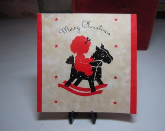 Colorful 1930's art deco christmas card red silhouette of of little girl in pajamas riding on her black and red hobby horse snowman inside