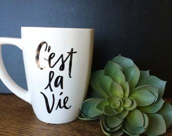 "Hand painted ceramic mug with delightful quote ""C'est la Vie"" (Such is Life), 12 oz. white"