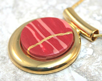 CLEARANCE SALE - Kintsugi (kintsukuroi) pendant in stripes of red and pink polymer clay with gold repair in a gold plated setting - OOAK