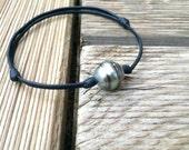 Tahitian circled pearl on black leather. Adjustable knots.