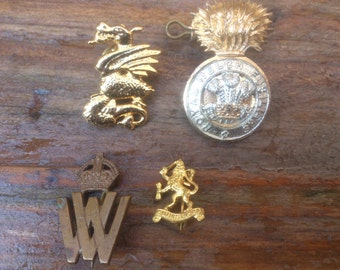 collection of four vintage military badges