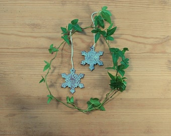 Set of two medium sized white (on red clay) ceramic snowflake stars ornaments with lace pattern.