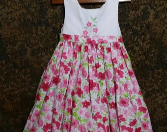 Adorable little girl quality vintage dress, adorned with red and pink daisies.