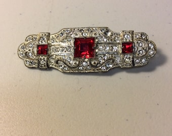 Crystal and ruby color stone pin.