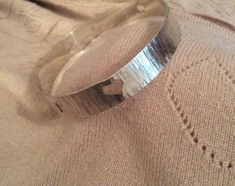 Hammered silver bangle with tiny cutout hearts. Made to order.