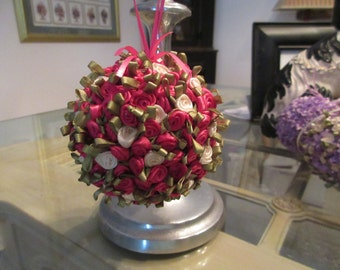 """Raspberry and Ivory 3"""" covered rosettes with green leaves peek a booing on this delightful ornament"""