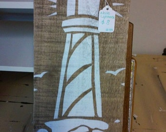 Stenciled lighthouse in white on reclaimed wood