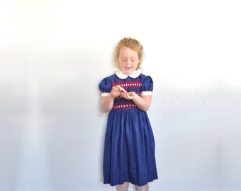 1960 smocked little girl dress . peter pan collar . traditional navy blue red embroidery