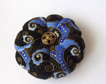 Pincushion Blue Mauve on Black Fabric . Great for a sewing gift - Round Pin cushion Double Sided swirls Taupe fabric with gold accents.