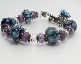 Lavender, turquoise, and dark purple lampwork beaded bracelet embellished with amethyst stones, swarovski crystals and Bali silver.
