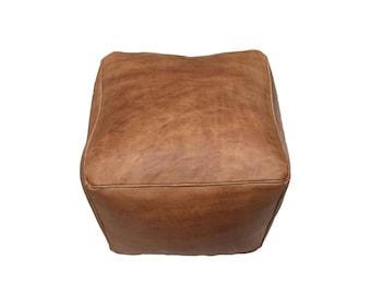 PUF otomano de cuero   cuero marrón natural. Cubo grande en la tierra.