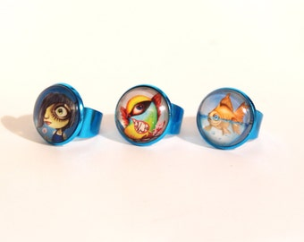 Shiny BLUE rings with lowbrow illustrations, art by Susann Brox Nilsen. Cartoon, comics, colorful, bird, best friend, punk, for her