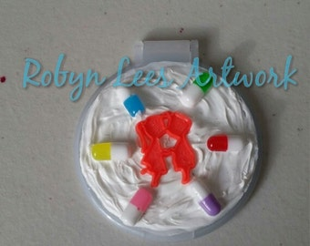 White Decoden Whipped Cream Topped Compact Hand Mirror with Fake Medication Pill Beads and a Boy & Girl in Love, Kissing