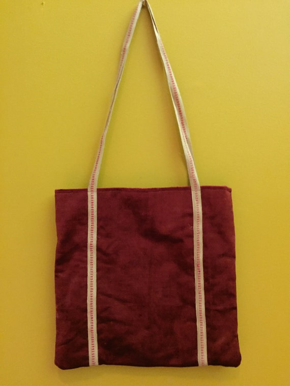 Beautiful red velvet tote with accent straps.