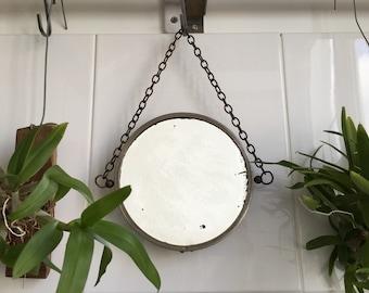 Round ancient mirror on chain.