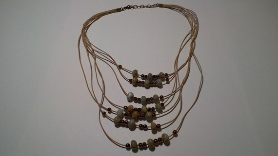 Necklace made of tan leather cord, brown colored hematite, and Impression Jasper beads