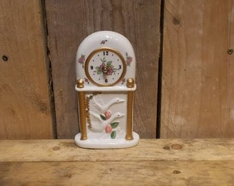 White swan table clock made of porcelain with gold leaf details.