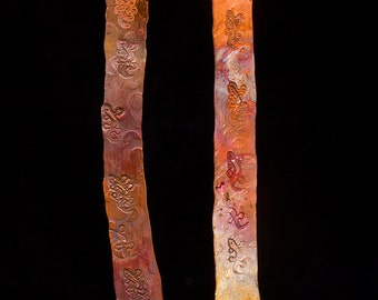 Long copper earrings stamped with geckos and a hand torched colourful patina