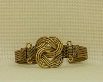 Brass bracelet with celtic knot motif.