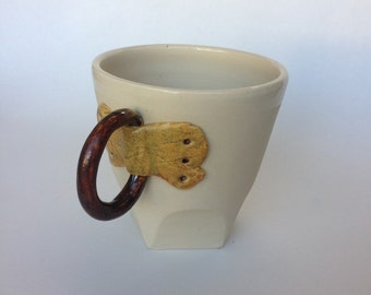 Ceramic pottery mug with buckle handle and altered faceted bottom