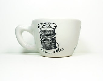 12oz cup with a spool of thread + needle prints, shown on White glaze - Made to Order / Pick Your Colour