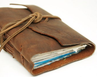 Mixed media leather-bound artist journal with feather