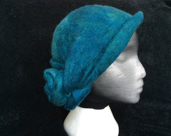 Hand made wet felted merino wool cloche style hat, peacock blue and teal blend with a double twist knot in the back