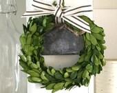 Boxwood wreath with striped ribbon, added galvanized chalkboard tin label.