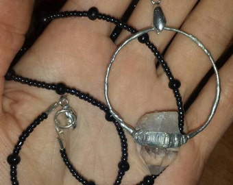 Clear quartz crystal pendant with oversized bail set in molten metal, on beaded necklace