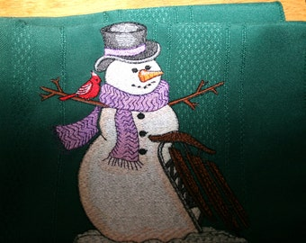 cloth napkin with embroidered snow man and sled