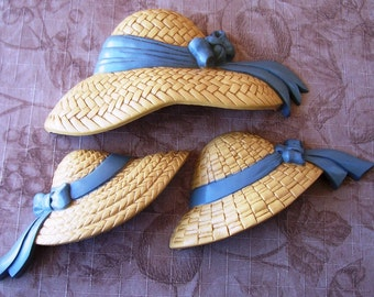 Vintage 1987 Burwood straw look hats with blue ribbon wall decor.    C7-185