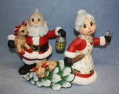 Handpainted Ceramic Santa Claus holding a baby deer and Mrs Claus pulling a tree with a baby deer sleeping in it