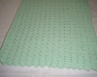 Light green crocheted acrylic baby blanket