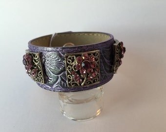 """Purple faux leather cuff featuring rhinestone pink flower trim. 1 1/4"""" wide, measures 8"""" from snap to snap"""