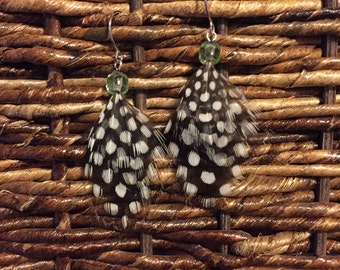 Feather earrings- black and white spotted feathers with a light green bead.