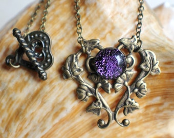 Morning glory heart necklace features a dichroic glass cabochon in purple tones.