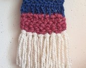 Handmade eggshell, pink and blue crochet wall decoration on golden wood post