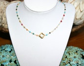 Quatrefoil in gold on multi colored rosary chain