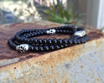 Handmade elastic wrap bracelet with black czech glass beads and sterling silver skulls
