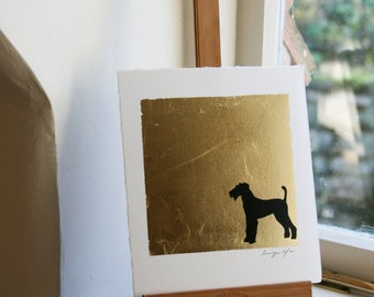 Hand drawn pen and ink silhouette of a dog on Gold leaf on paper.