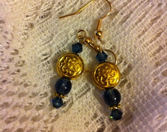 Dark montana blue Swarovski and gold plated pierced earrings with Celtic knot beads.