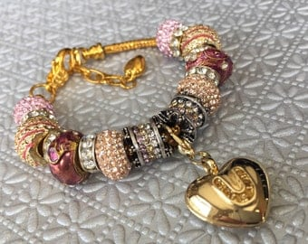 "Gold tone mauve and crystal  "" I love u""  charm bracelet."