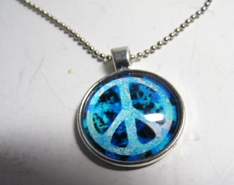 Hand made necklace with glass cabachon, depicting a retro PEACE sign. With ball chain