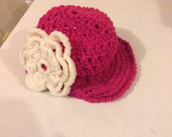 Beanie hat with brim and flower.