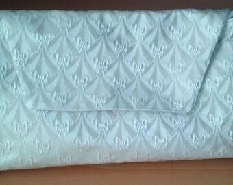 Cream bow pattern clutch bag