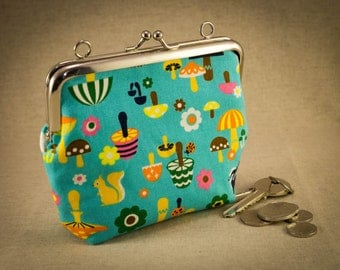 Turquoise coin purse with woodland animals.  Silver coloured kiss lock snap frame.  Rabbits, squirrels, hedgehogs and toadstools
